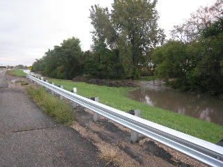Water begins to rush eastward through the ditches of Highway 68 as water spills the river banks before going under the Highway 68 bridge.