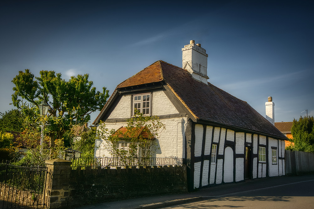 Timber-framed cottage with white rendered walls and black-painted beams by the side of a road
