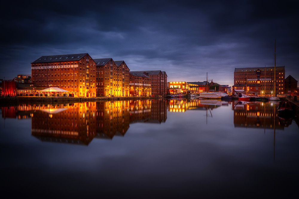 Night view of old warehouses converted to apartments lit up and reflected in the water of the main basin around which they stand