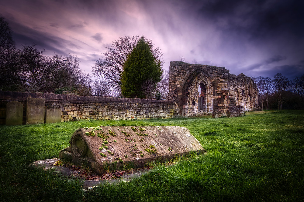 Photo of the ruined wall of the priory under stormy skies with a 19th-century tombstone laid into the grass in the foreground