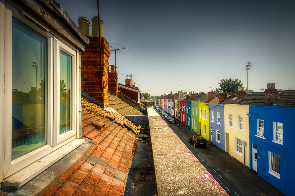 Roof top view of street lined with humble, brightly-painted, two-storey terraces