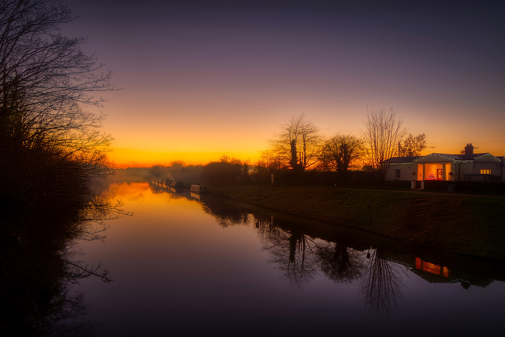 Glowing sunset view down tree-lined canal with narrowboats moored in distance and porch of bridge-keepers cottage lit, all reflected in the flat-calm waters of the canal
