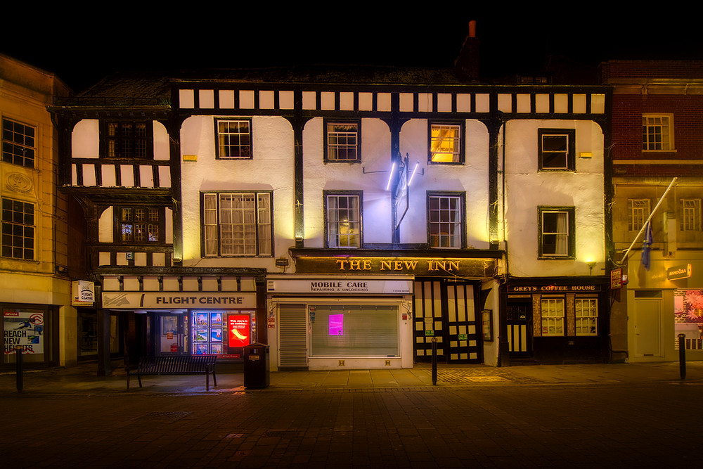Night shot of the three-storey, five-bay, timber-framed New Inn with a single top-floor room light on illuminating part of a wood-beamed ceiling