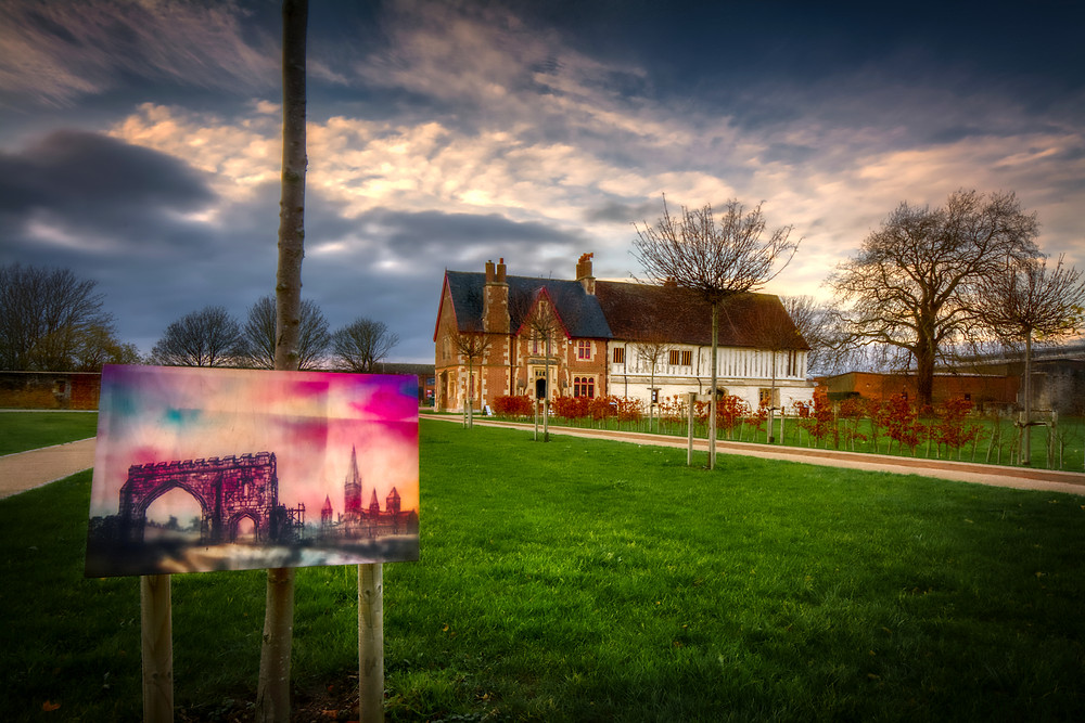 Photo of building in background with, in the foreground, painting of gate and church spire on display in the priory grounds