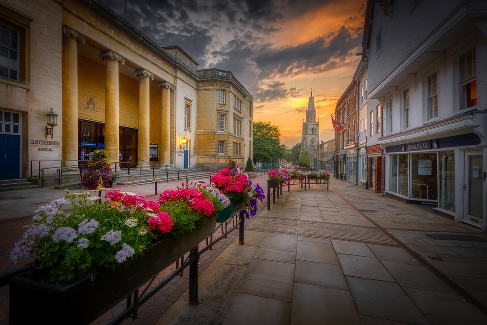 Photo looking down the street under a colourful sunset to the spire of St. Nicholas Church, with shops on the right, the columned portico of Shire Hall on the left and colourful planters in the foreground