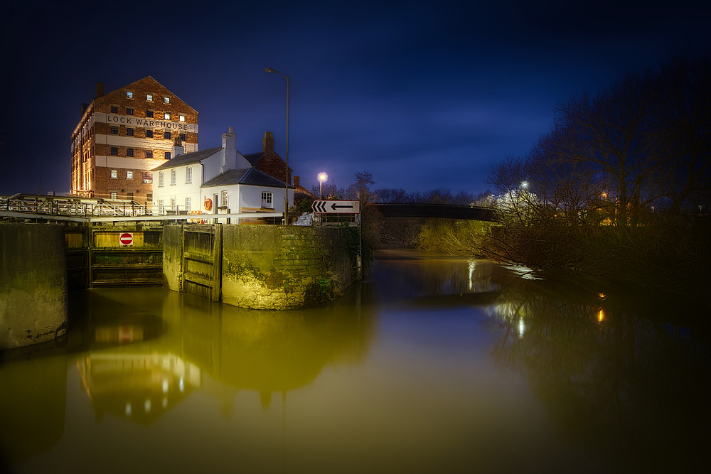 Night view of Gloucester Lock and white lock-keep's cottage to left, River Severn to right, and Lock Warehouse towering above in background