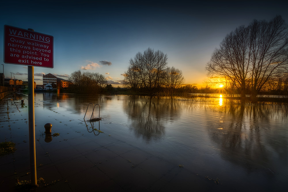Sunset view of River Severn flooding quay in foreground and Alney Island, immediately to the west of the city centre, in background