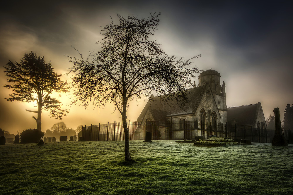 Fog lifting on an early morning view of crematorium surrounded by gravestones with a couple of leafless trees growing from the cemetery lawn