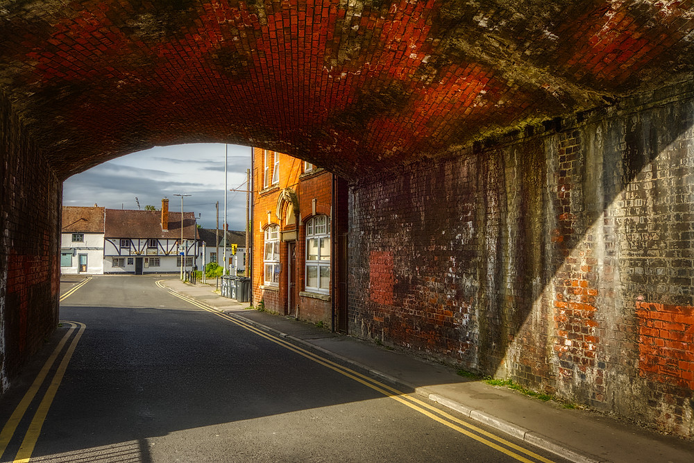 Photo looking through the arch of a railway viaduct up Hare Lane to a 16th-century timber-framed building