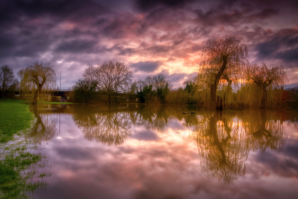 Purple and orange sunset sky reflected in floodwaters of the Severn with purely functional steel and concrete bridge in the distance