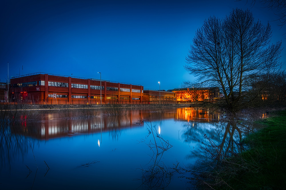 After dark photo of the Severn in flood with, on the opposite bank, the modern day administration block of Gloucester prison, which currently occupies the site of Gloucester Castle