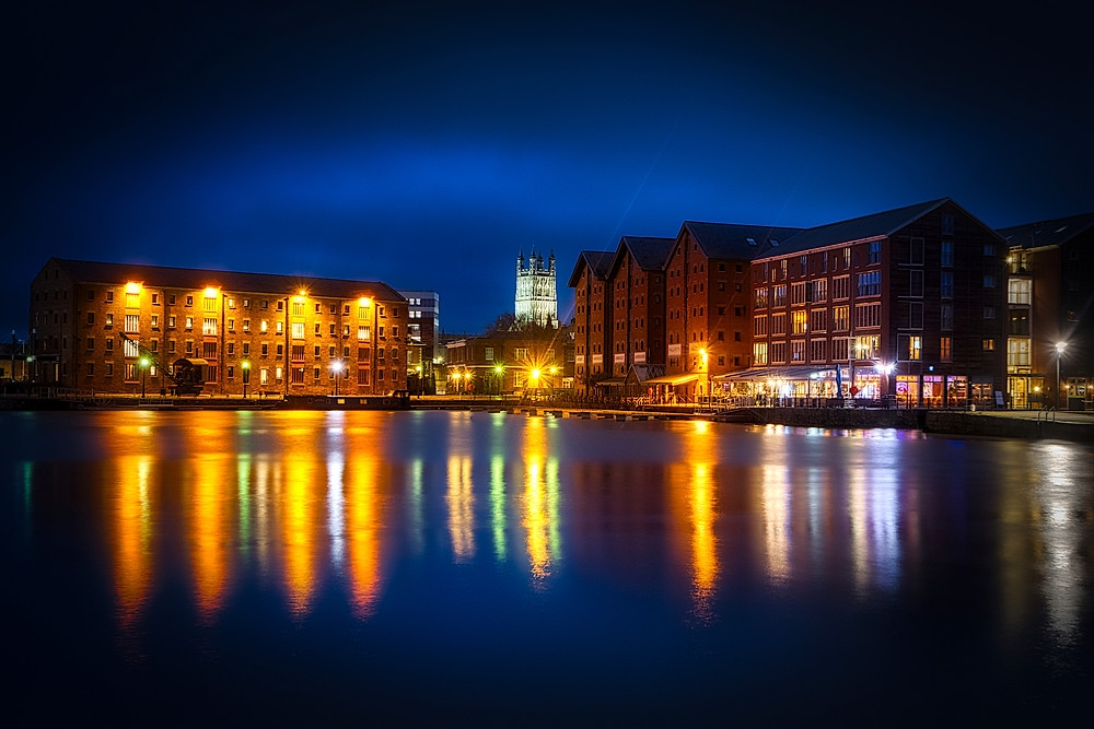 Night view of main basin lined with old warehouses and a modern apartment block, with tower of Gloucester Cathedral in background and lights reflected in the water
