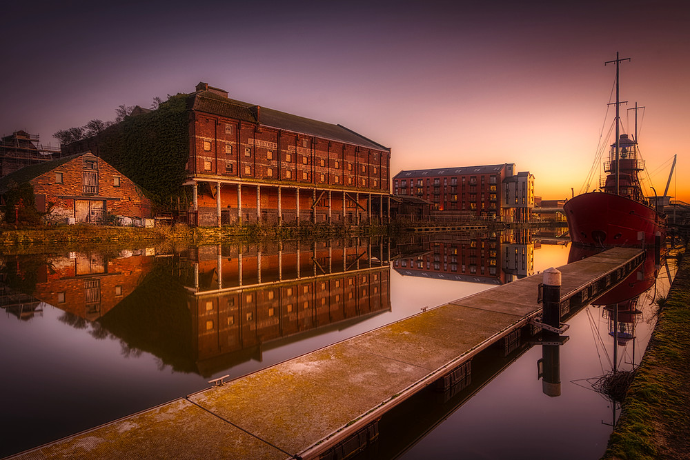 Sunset view of a derelict warehouse reflected in the flat-calm canal waters with an old lightship moored opposite