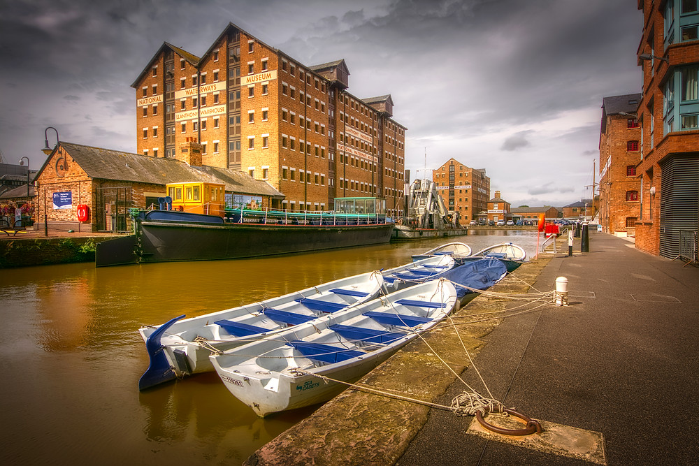 View of old warehouse now converted to museum towering over a small narrow arm of the docks' main basin with sea-cadet rowing boats moored in the foreground