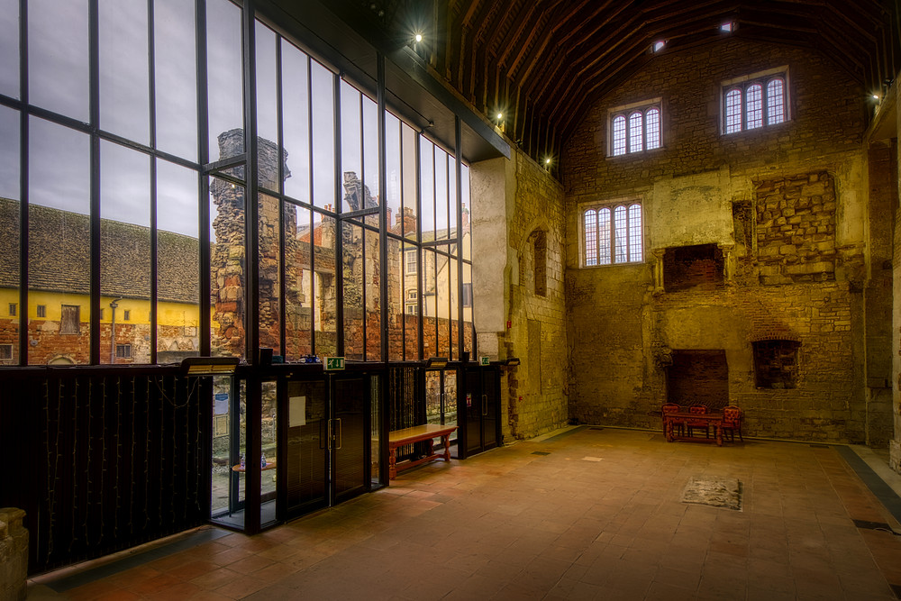 Photo of the great hall in the former church with a view out of the glazed wall to courtyard ruins