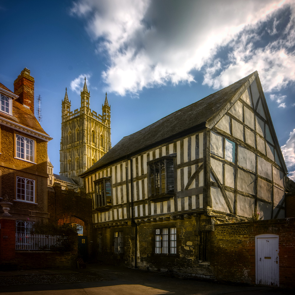 Photo of a timber-framed house with the tower of Gloucester Cathedral in the background