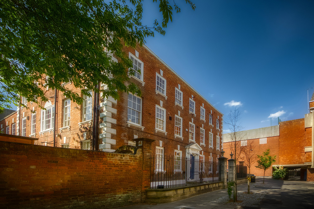 Large, elegant, three-storey, brick-built property in foreground, behind which is effectively a featureless wall just as tall with a dark, enclosed alley in the bottom right corner