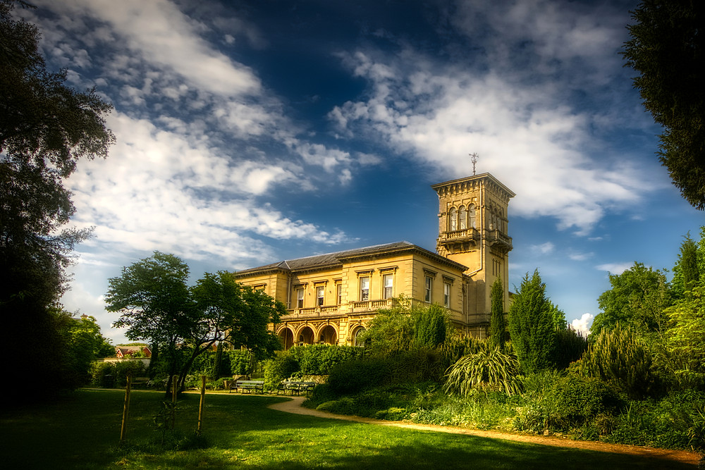 Ornate, italianate-style mansion of two storeys and a square tower set in lush green gardens