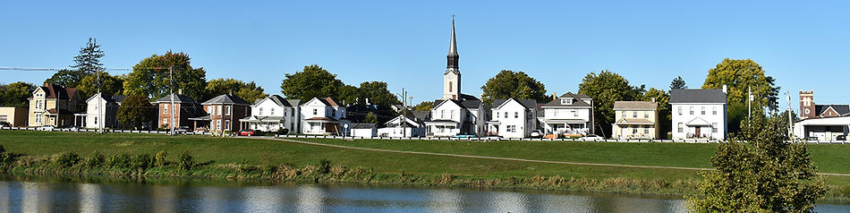 Houses in a row by river with church in