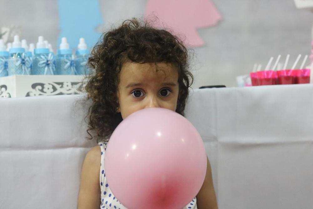 Criança enchendo balão