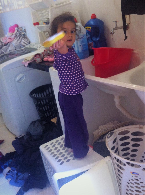 Criança aprontando e lavando roupa