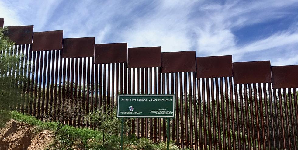"Brown border wall with green sign in Spanish stating ""limite de los estados uniods Mexicanos"""