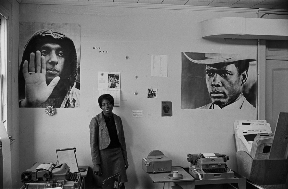 Barbara Howard Flowers at the Southern Courier office in the Frank Leu Building in Montgomery, Alabama. Posters of Stokely Carmichael and Sidney Poitier are on the wall behind her. Flowers held several positions at the Courier, including compositor and associate editor. (1968)
