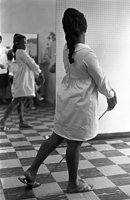 Girl standing in front of a mirror in a beauty salon in Montgomery, July 1966.