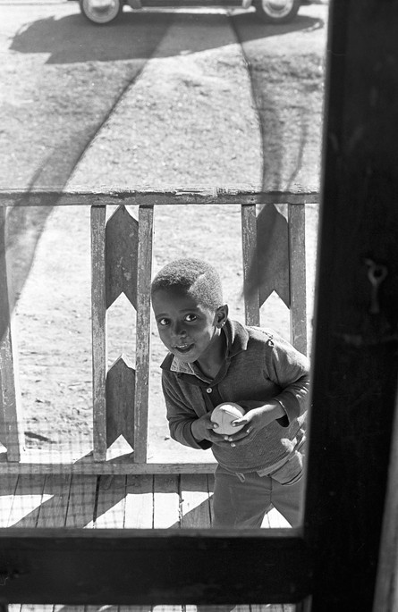 Little boy looking through a screen door from the front porch of a house, circa 1965-1968.