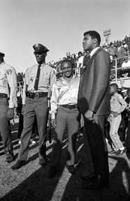 Muhammad Ali at the football game between Alabama State College and Tuskegee Institute on Thanksgiving Day, 1966. Montgomery police officer Sidney Williams and disc jockey Al Dixon are standing with him.