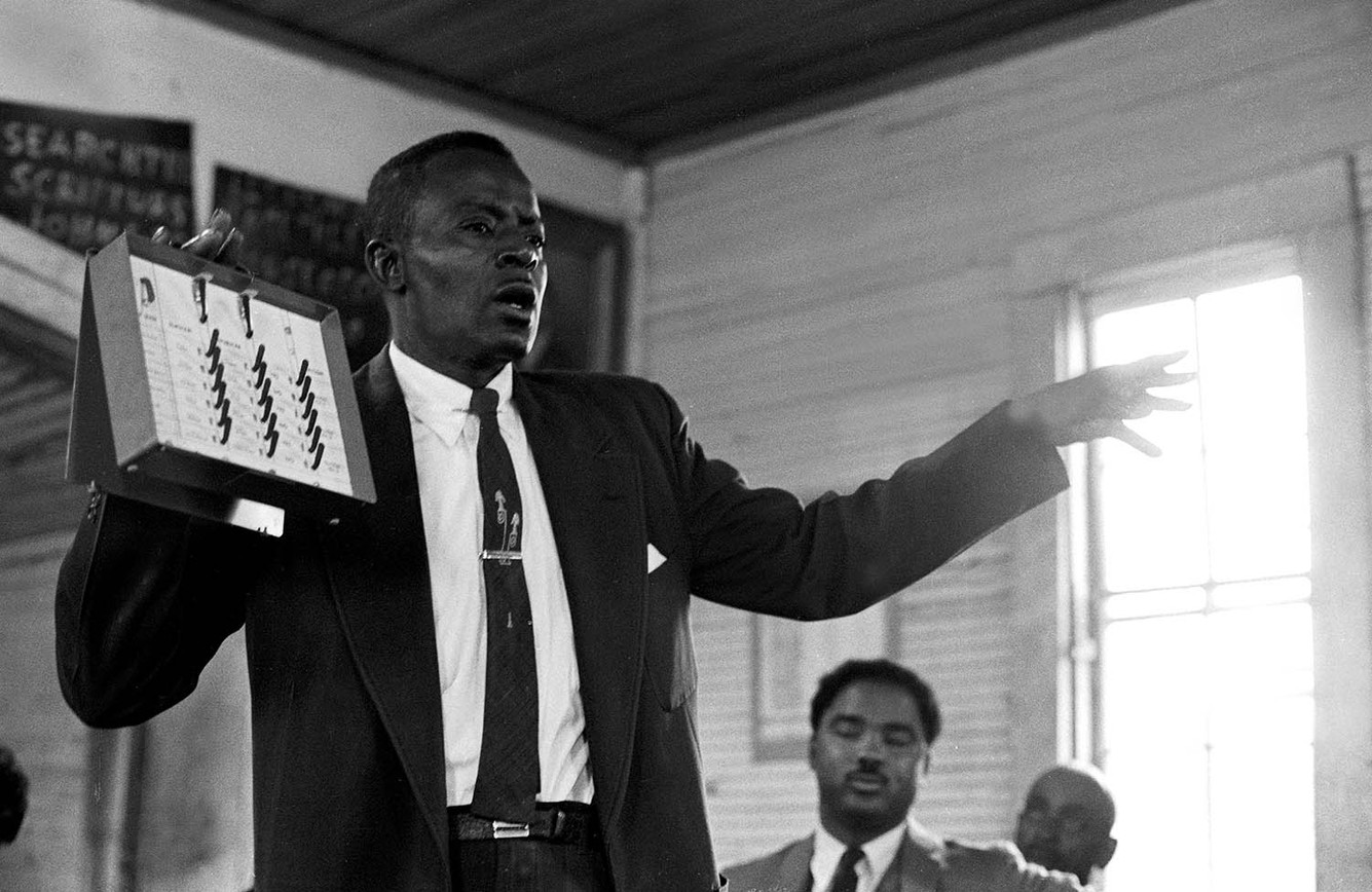 Willie Lee Wood, Sr., holding a voting machine during a demonstration in Autauga County, 1966. Wood, who was the first African American to run for office in Prattville, ran unsuccessful campaigns for coroner (in 1966) and city council (three times). In 1988 his son, Willie Lee Wood, Jr., became the first African American to hold public office in the city when he was elected to the city council; he served for 28 years, longer than any other elected official in Prattville history.