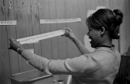 Viola Bradford working at the Southern Courier office in the Frank Leu Building in Montgomery, Alabama. Bradford was a reporter for the Courier from 1965 to 1968. She is holding up a headline from the front page of the issue for January 22-23, 1966. (1966 January)