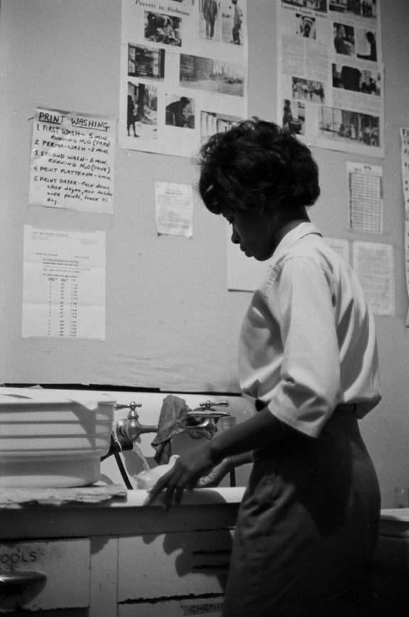 Luella Adams in the darkroom used by Southern Courier staff in Montgomery, Alabama. Adams was a darkroom technician for the Courier. The main office for the Southern Courier was at the Frank Leu Building in downtown Montgomery, but at some point the staff used darkroom set up at Jim Peppler's apartment in Clifford and Virginia Durr's house on Felder Avenue. (1965-1968 circa)