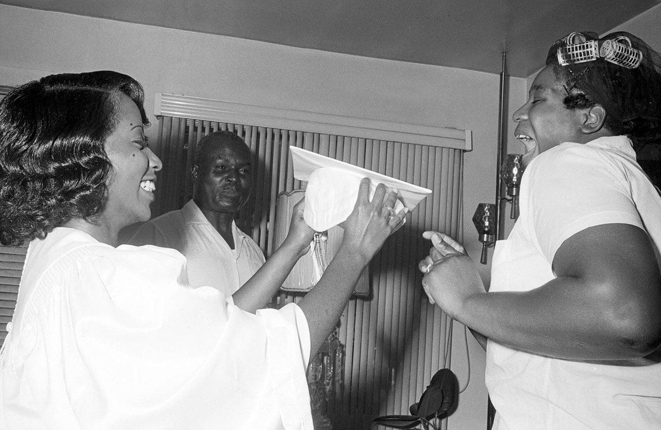 Susie Sanders putting on her cap and gown before her graduation from Sidney Lanier High School in Montgomery, May 1967. Sanders was one of the first African American students at Lanier.