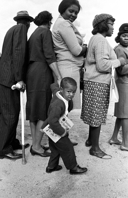 Members of the Lawson family waiting to vote in Lowndes County, November 1966. In line are John Collins Lawson, his wife, Zeola Bradley Lawson, his daughter-in-law, Novella Lawson (holding her baby, Sharon), and his grandson, Ted Lawson (who is holding a spelling book). J. C. Lawson was a farmer, minister, teacher, and school principal, and he was the first person in Lowndes County to pass the literacy test that had been required for voter registration. Because Lawson was partially blind he walked with a cane (white with a red tip), which he is carrying in this photograph. Mattie Kate and Rosie Mallard (sisters-in-law) are standing in line in front of the Lawson family.