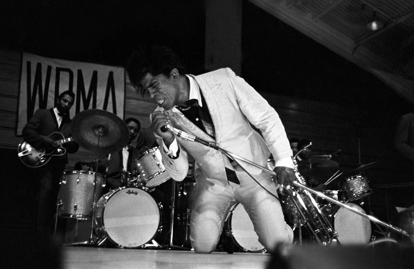 James Brown performing at the Alabama State College Arena in Montgomery, circa 1965-1968. A banner for WRMA, a local African American radio station, is hanging in the background.