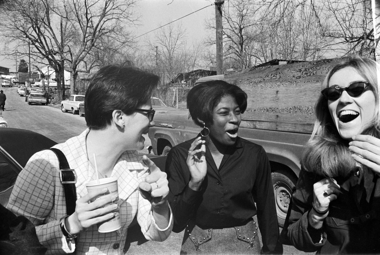 Amy Peppler, Barbara Howard Flowers, and Mary Ellen Gale laughing together in a street in Montgomery Alabama. Peppler, wife of photographer Jim Peppler, was the Southern Courier's layout editor; Gale was a reporter for the paper from 1965 to 1968 and served as the executive editor from 1966 to July 1968; and Flowers also held several positions at the Courier, including compositor and associate editor. (1968 circa)