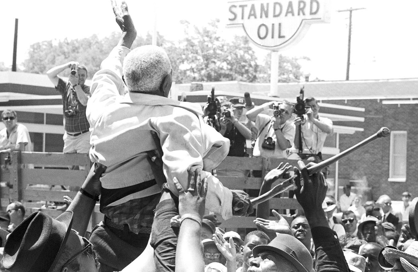 """Ed Fondren being lifted above a crowd in Batesville, Mississippi, during the """"March Against Fear,"""" 1966. Fondren, who was 106 years old, had just registered to vote for the first time."""