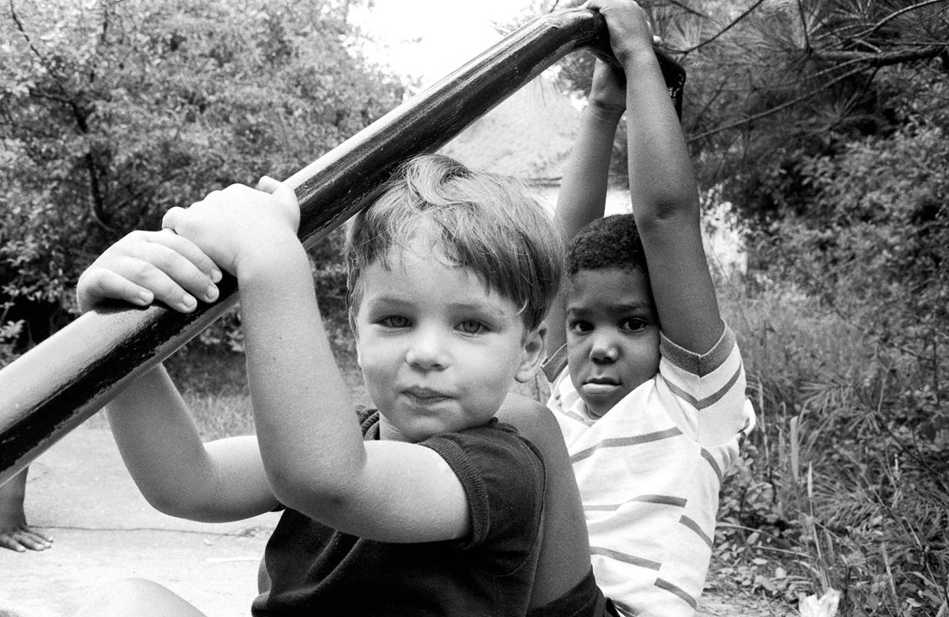 Two little boys outside a building, possibly while attending a summer program, circa 1965-1968.