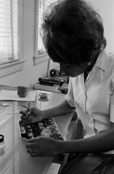 Mary Corbin selecting frames from a contact sheet at the Southern Courier office in the Frank Leu Building in Montgomery, Alabama. Corbin was a compositor for the Courier from June 1967 to December 1968. (1967-1968 circa)
