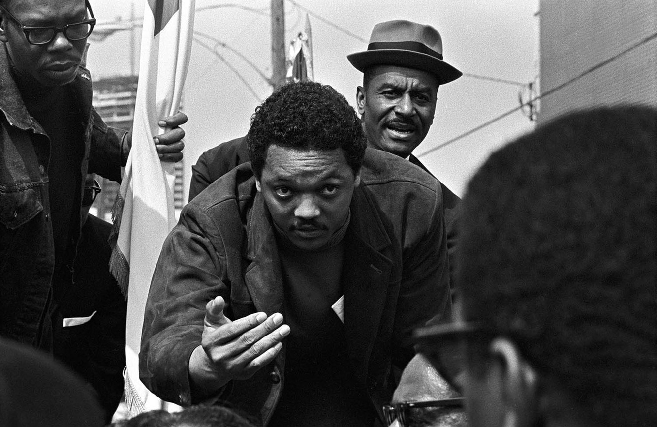 Jesse Jackson on the cart with Martin Luther King Jr.'s casket in Atlanta, April 9, 1968. T. Y. Rogers and Fred Shuttlesworth are with him.