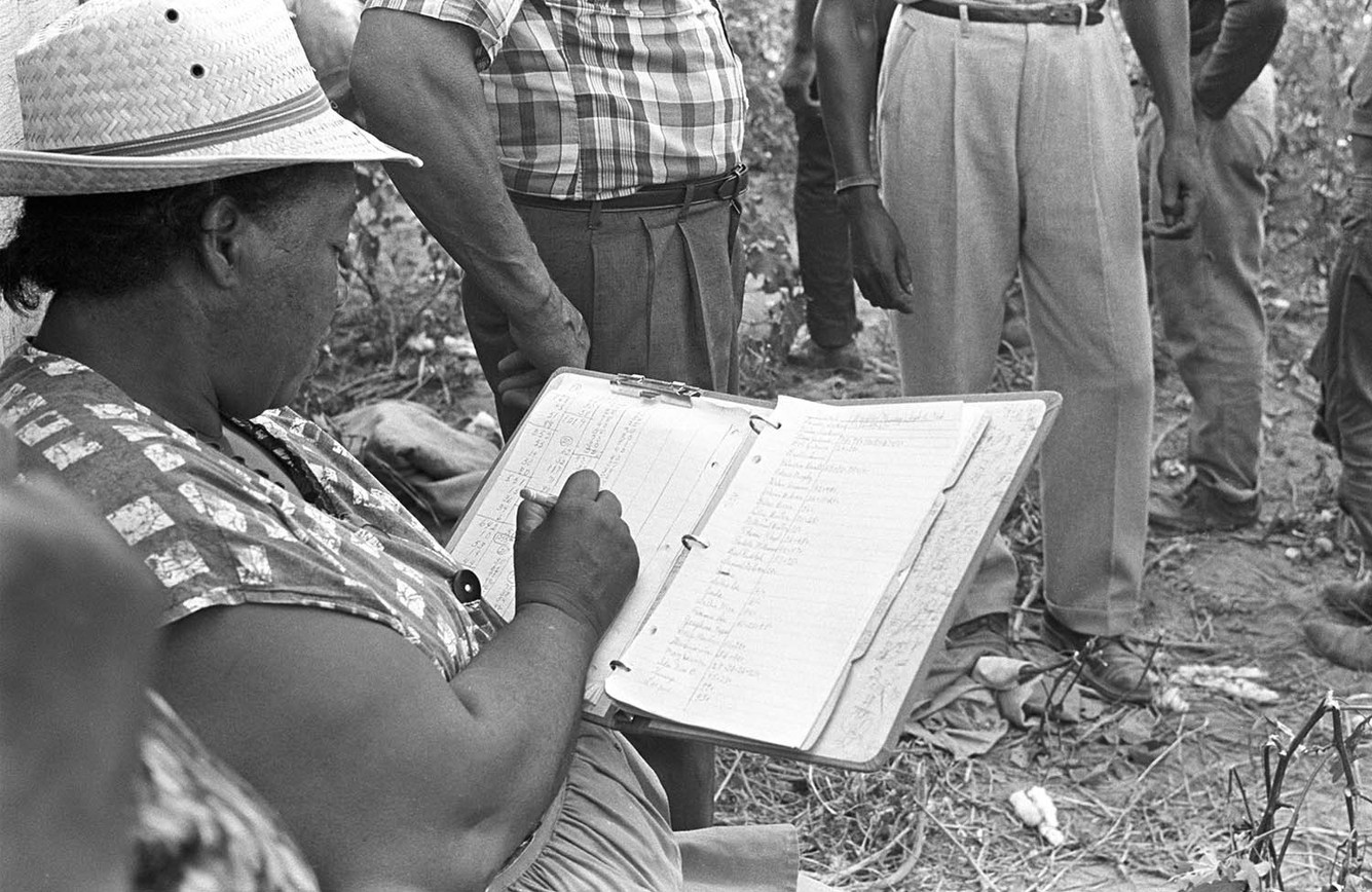 Minnie B. Guice making notes about cotton picked from her field in Mount Meigs, September 1966.