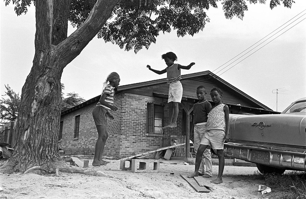 Elizabeth Ellis and Diane Foster playing on a seesaw made of wooden planks and cinderblocks in Newtown, August 1967. Robert Harris and Angelina Foster are standing on the right.