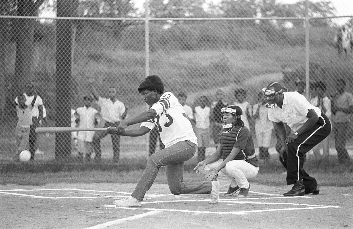 Young woman at bat during a softball game in Montgomery, July 1967. Cessie Ree Cooper is playing catcher, and Ralph Featherstone, an employee of radio station WRMA, is the umpire.