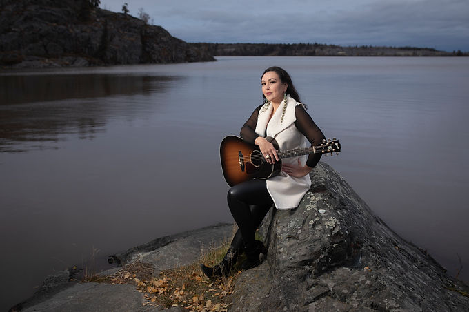 Leela Gilday sitting on a rock beside a lake holding a guitar.