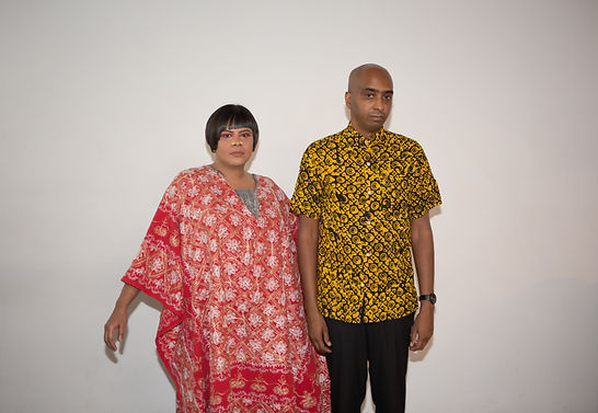 Rosina wearing a red dress and Nic wearing a yellow and black shirt in front of a white background.