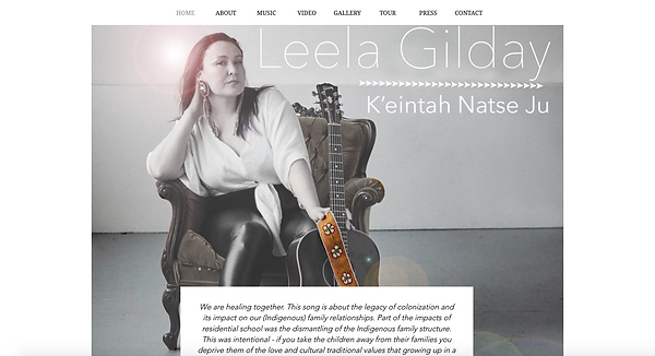Leela Gilday sitting in a chair holding her guitar with text of thehom page of her website