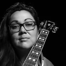 An Indigenous woman holding a guitar in a black and white image.