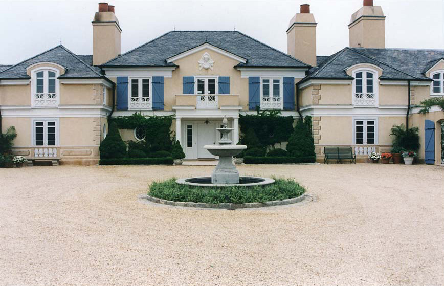 The architectural stone elements and the first floor French doors are painted directly on the stucco