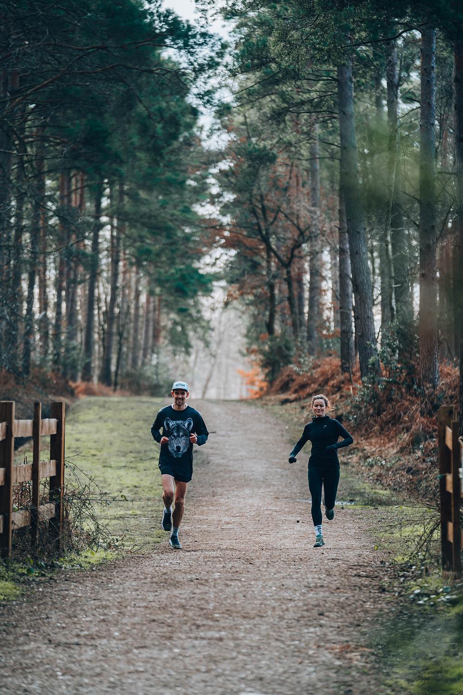 KOTWF athlete Arne Dumez and physiologist and pilates instructor Esther Goldsmith runs through Swinley Forest while smiling
